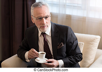 Delighted bearded businessman drinking coffee in the hotel