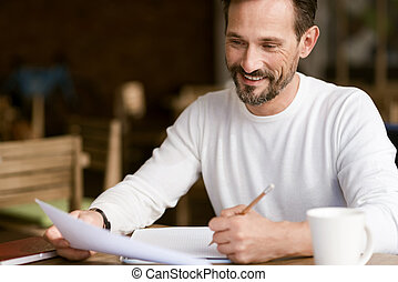 Delighted bearded man making notes in the cafe