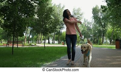 Delighted beautiful woman walking with her dog