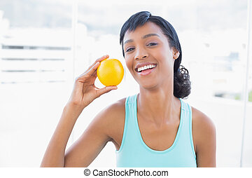 Delighted black haired woman holding an orange