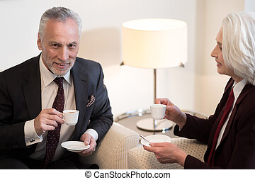 Delighted businessman having a break with his colleague