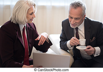 Delighted businesswoman and her colleague working with the laptop