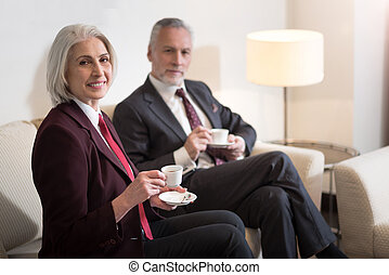 Delighted businesswoman drinking coffee with her colleague