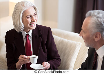 Delighted businesswoman having the conversation with her colleague