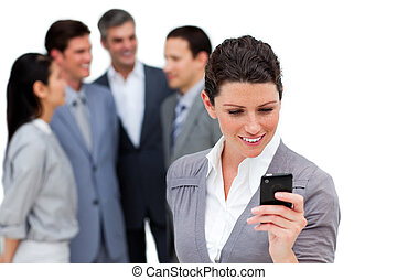 Delighted businesswoman using a mobile phone in front of her team