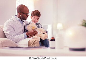 Delighted cheerful male doctor treating his patient