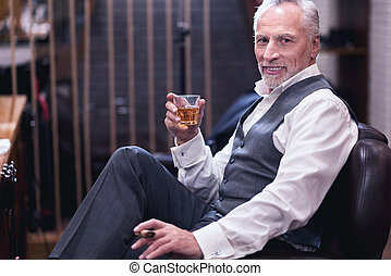 Delighted cheerful man holding a glass with whisky