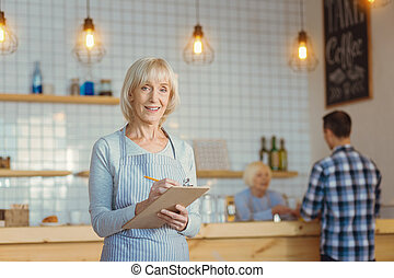 Delighted cheerful woman working in the coffee shop