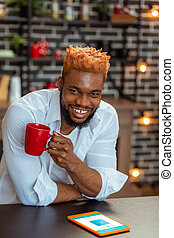 Delighted cheerful young man drinking his coffee