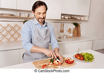 Delighted cook cutting pepper for dinner in the kitchen