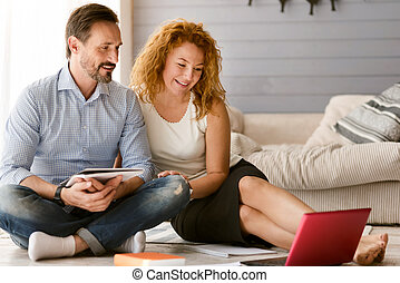 Delighted couple enjoying freelance job at home