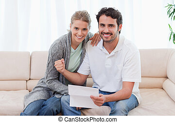 Delighted couple reading a letter in their living room