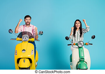 Delighted crazy two people lucky wife husband extreme sport lovers celebrate electric scooter ride lottery sit raise fists scream yes wear striped pink shirt isolated over blue color background