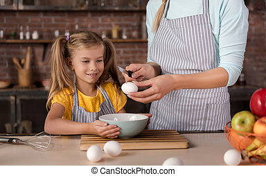 Delighted daughter cooking with her mother in the kitchen