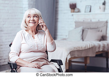 Delighted disabled lady using phone at home