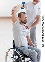 Delighted disabled man exercising with his assistant in the gym