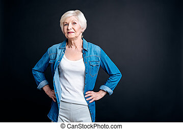 Delighted eldely woman standing on black background