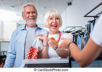 Delighted elderly couple finishing their weekend shopping