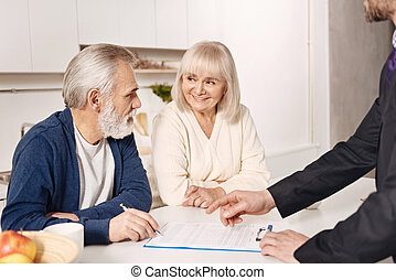 Delighted elderly couple signing agreement at home