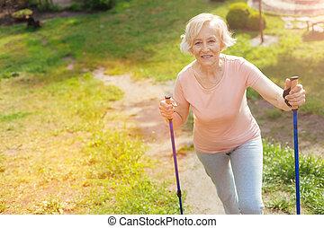 Delighted elderly woman enjoying her walk