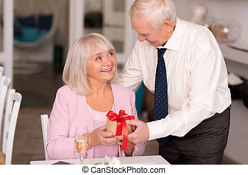 Delighted elderly woman holding a present