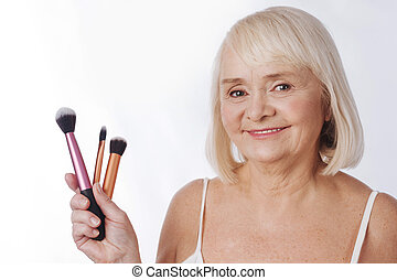 Delighted elderly woman holding cosmetic tools