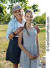 Delighted elderly woman hugging her granddaughter