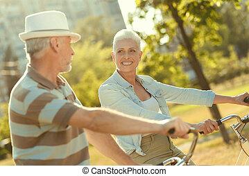 Delighted elderly woman hugging her husband