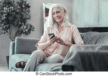 Delighted elderly woman using her smartphone