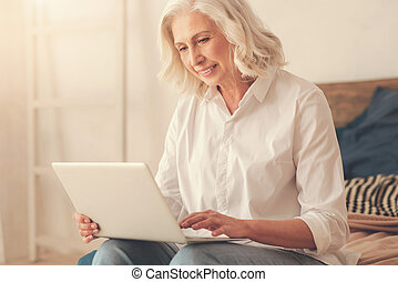 Delighted elderly woman working on a laptop