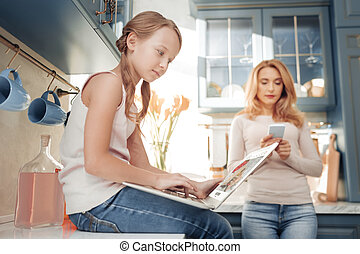 Delighted female teenager using her gadget in the kitchen