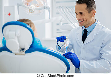 Delighted friendly doctor talking to his patient