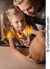 Delighted girl preparing a pumpkin for Halloween with her mother