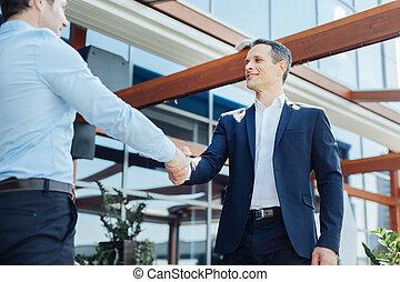 Delighted handsome businessmen shaking hands