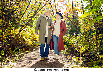 Delighted happy couple walking together in the forest