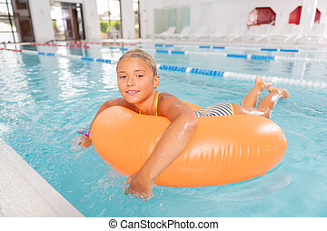 Delighted happy girl enjoying time in the pool