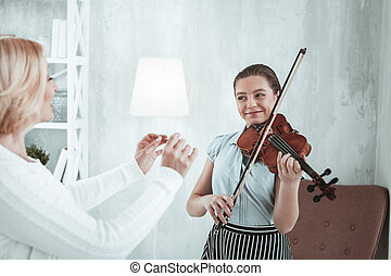 Delighted happy girl having a violin lesson
