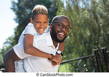 Delighted happy man carrying his son on the back