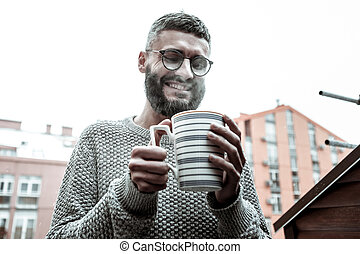 Delighted happy man wanting to drink his coffee