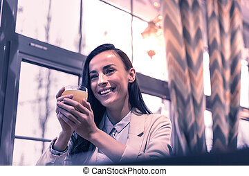Delighted happy woman giving holding a glass of juice