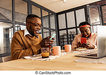 Delighted joyful couple being engaged in their smartphones