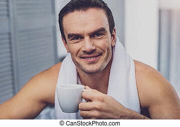 Delighted joyful man having coffee