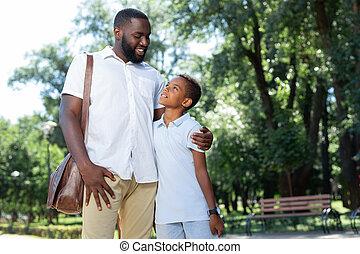 Delighted joyful man hugging his beloved son