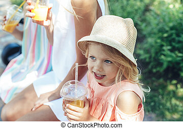 Delighted kid drinking juice with family outside