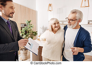 Delighted lawyer offering contract to aged couple of clients