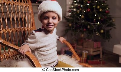 Delighted little boy sitting in the rocking chair