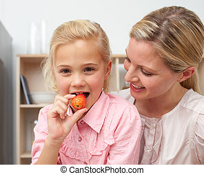 Delighted little girl eating fruit with her mother