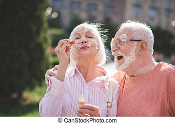 Delighted man and woman spending time with pleasure outside
