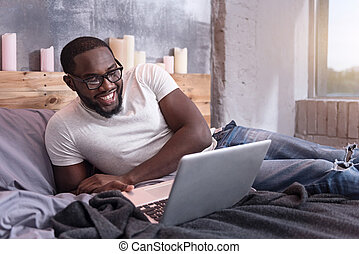 Delighted man using laptop in bedroom
