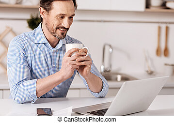 Delighted mature businessman enjoying freelance work at home